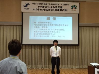 <p>前田晃教君と参加者による綱領指針の唱和の様子。<br />新入会員にもわかりやすくスクリーンに表示されています。</p>