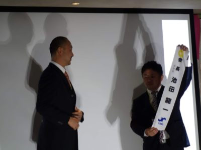 新役員紹介 池田龍一会長予定者顕太郎会長からタスキがかけられます